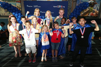"St. Joseph's Children's Hospital President Kimberly Guy poses with ""superheroes"" during the 17th annual Kids are Heroes celebration at the Tampa Bay Times Forum. Parents, teachers, guidance counselors and neighbors nominate children for doing heroic acts ranging from saving someone's life to raising money for pediatric cancer awareness to caring for an injured animal. Since 1996, St. Joseph's Children's Hospital in Tampa, FL, has recognized more than 1,600 children who have performed heroic deeds or displayed acts of selflessness and good citizenship. (PRNewsFoto/St. Joseph's Children's Hospital)"
