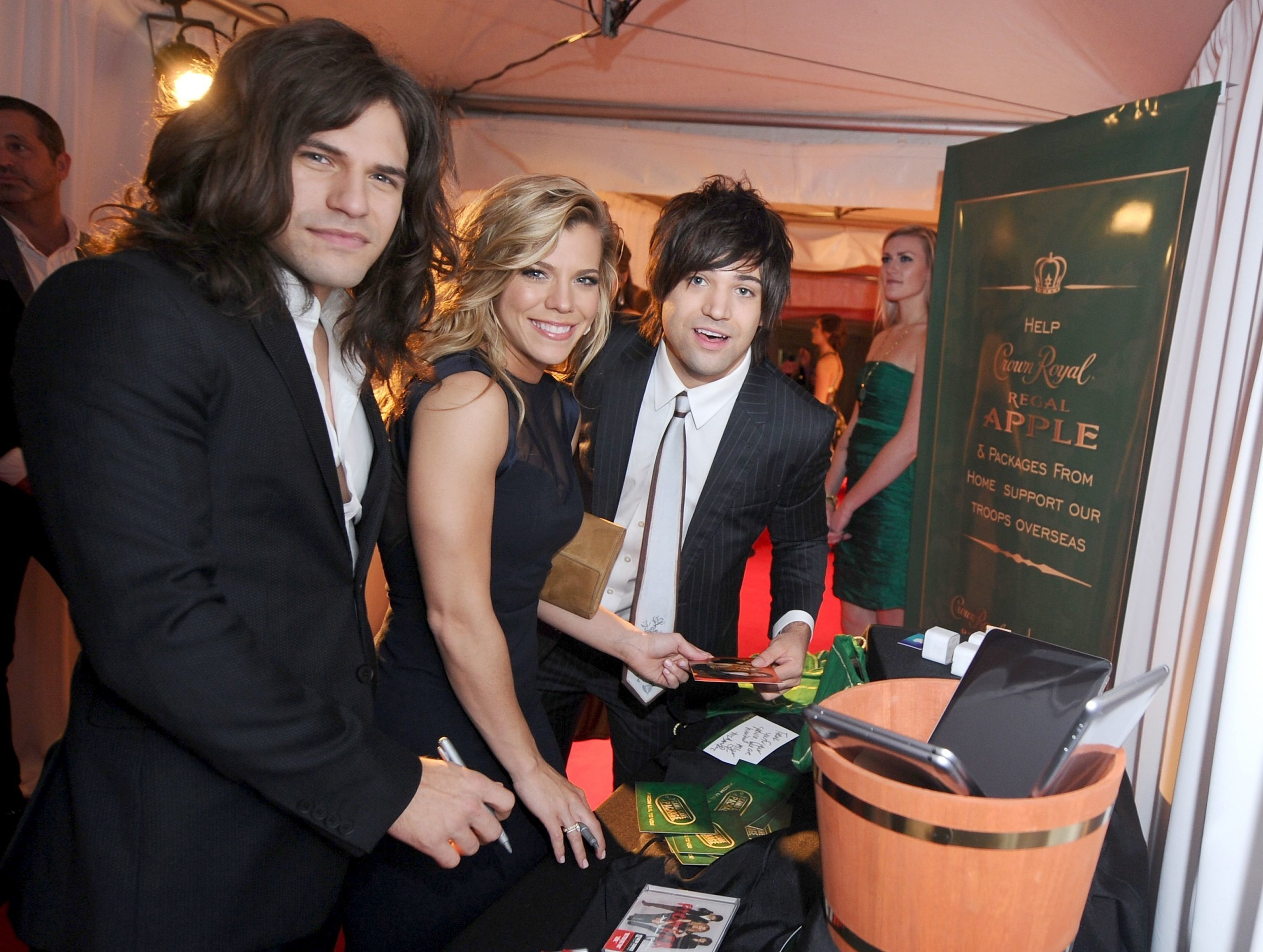Reid Perry, Kimberly Perry, and Neil Perry of The Band Perry take a moment to pack a Crown Royal Regal Apple care package in effort to honor US troops overseas at the BLMG After Party on November 5, 2014 in Nashville, Tennessee. (Photo by Ilya S. Savenok/Getty Images for Crown Royal)