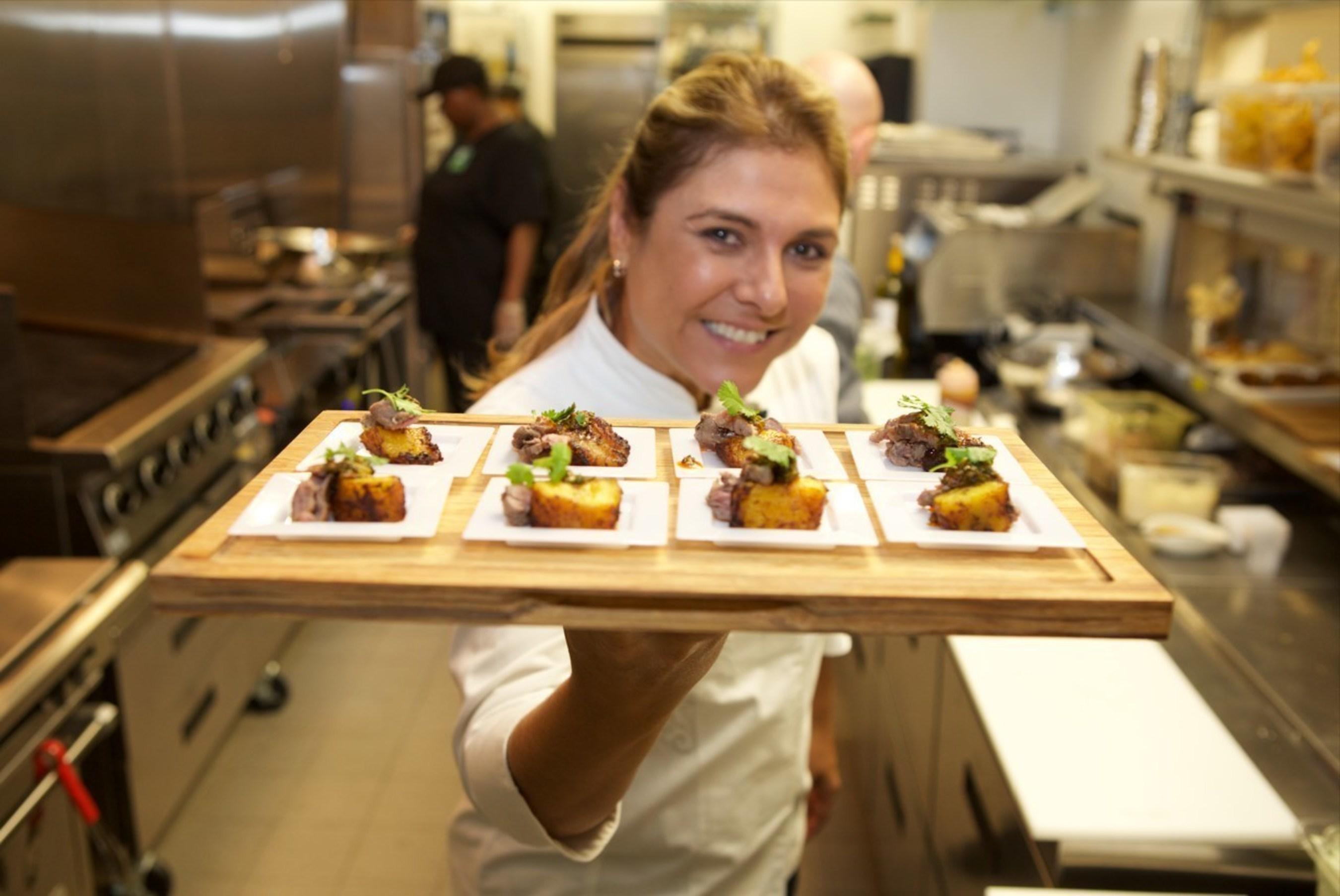Chef Lorena Garcia showing off her vibrant menu of Tapas