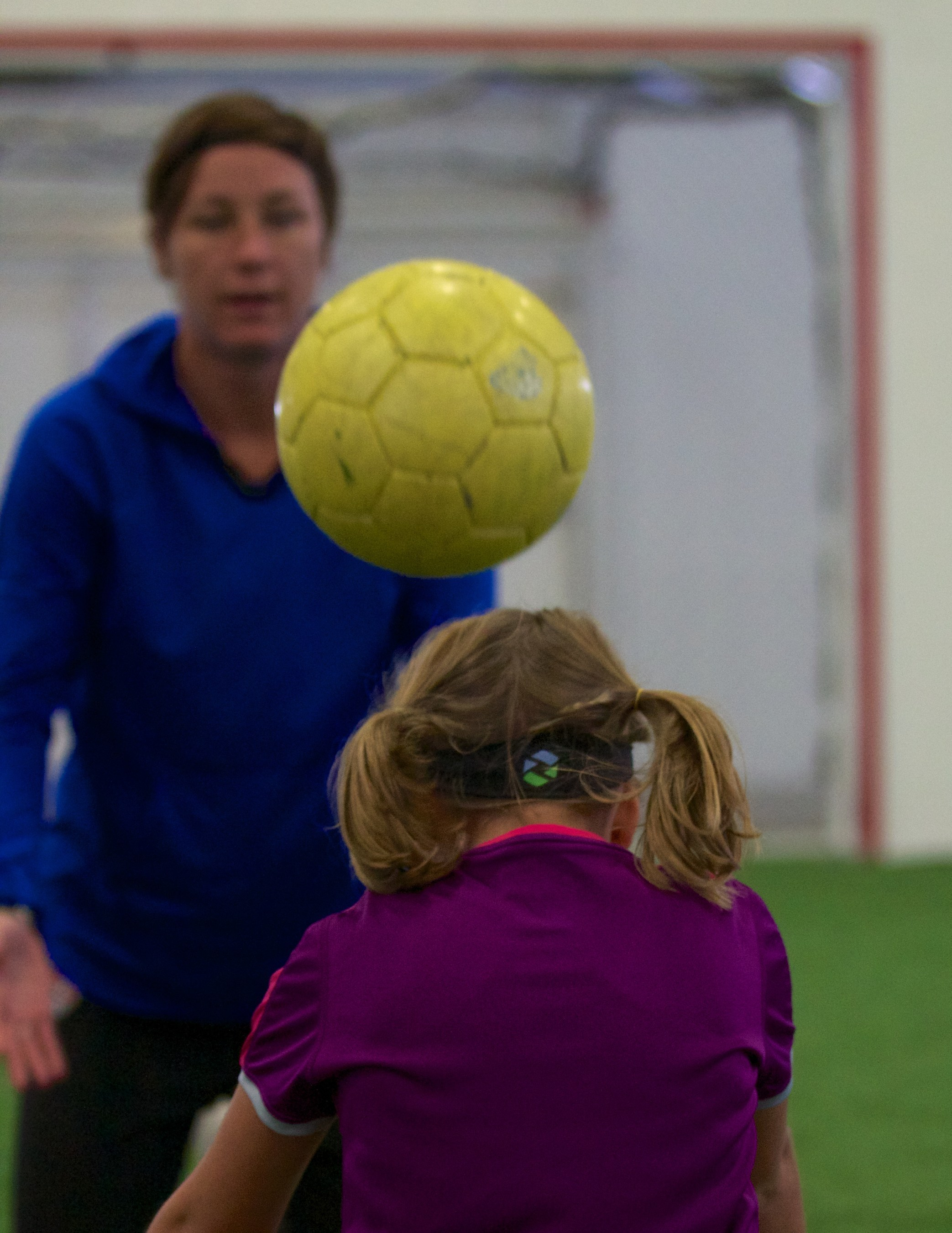 Abby Wambach, USWNT all-time leading scorer, trains young player wearing the Triax SIM-P head impact monitoring device.