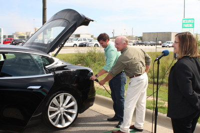 Matthew Budraitis and Don Ketcham, Farley engineers, plug-in an electric vehicle to officially open the charging stations as Farley Site Vice President Cheryl Gayheart looks on.