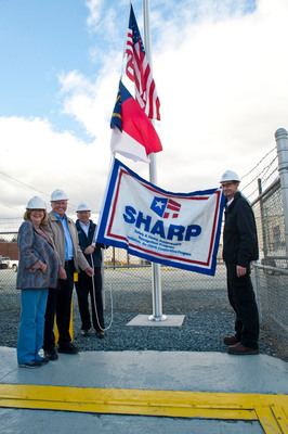 "NCDOL Commissioner Cherie Berry, left, presents the Safety and Health Achievement Recognition Program (SHARP) flag to Walter ""Junior"" Speas, Manager of Terminal Operations, David Brinkley, Director of Logistics, and Lance Clinard, Assistant Terminal Manager of Roanoke Cement Company for 15 years without a lost time accident.  (PRNewsFoto/Roanoke Cement Company)"