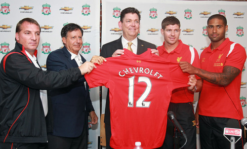 (Boston) Liverpool FC Chairman Tom Werner (left), Manager Brendan  Rodgers (2nd  from left) Captain Steven Gerrard (2nd from right) and  Right-Back Glen Johnson  (right) present Chevy VP of North American Marketing Chris Perry (middle) with  an official Liverpool FC jersey as  part of the club's sponsorship announcement  with global auto maker,  Chevrolet. Chevrolet announced Tuesday afternoon at Fenway Park that it has entered into a four-year partnership agreement with Premier League giant to become the club's Global Official ...