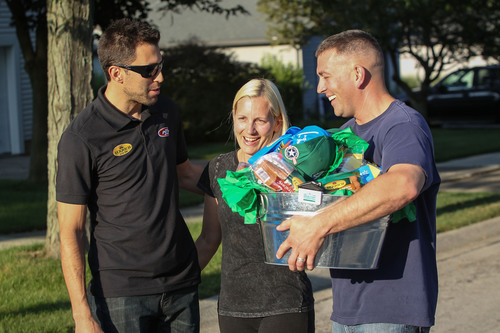Eckrich and NASCAR driver Aric Almirola surprise active duty military member Howard Kott and his wife, Dawn, at their Ann Arbor home.  (PRNewsFoto/Eckrich)