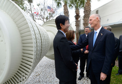 Beside a massive turbine on display outside the Orlando manufacturing campus of Mitsubishi Power Systems Americas, Florida Governor Rick Scott discusses his job creation strategies with Koji Hasegawa, Mitsubishi Power Systems Americas president and CEO following the Governor's announcement that the state's unemployment rates have fallen below the national average. Joining them is Bob Provitola, MPSA's general manager at the Orlando facility. (PRNewsFoto/Mitsubishi Power Systems Americas, Inc.) (PRNewsFoto/MITSUBISHI POWER SYSTEMS...)