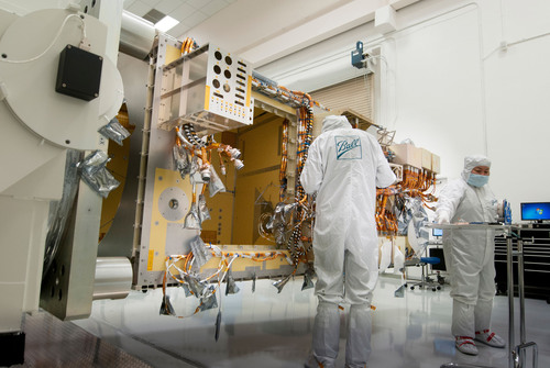 Ball Aerospace technicians install wire harnessing on the Joint Polar Satellite System-1 satellite. Ball has ...