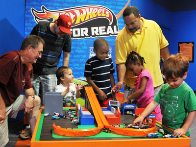 "Hot Wheels(R) are one of the toys included in ""100 Toys (& their Stories) that Define Our Childhood"" organized by The Children's Museum of Indianapolis. Families enjoying time together in the new exhibit Hot Wheels For Real(TM) at The Children's Museum."