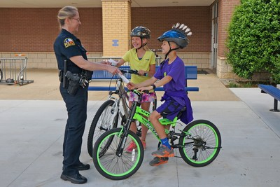 "A police officer ""tickets"" kids with a 7-Eleven Operation Chill coupon for being safe by wearing helmets while riding their bikes."