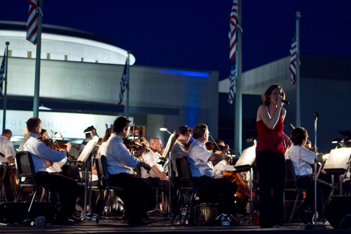 The Brazos Valley Symphony Orchestra and Kelsey Taylor perform the national anthem at the College Station Noon ...