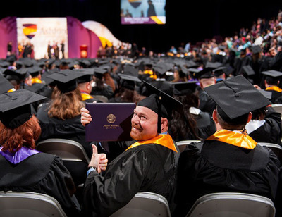 Tom Hoffmann receives Ashford University diploma on behalf of his daughter, Sidney, who is currently serving in Afghanistan.  (PRNewsFoto/Ashford University)