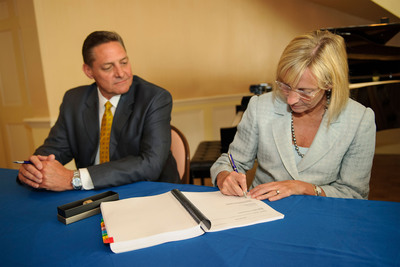 Philips Healthcare Americas President Steve Laczynski looks on as Philips Healthcare Chief Executive Officer Deborah DiSanzo signs a contract announcing an alliance with the Georgia Regents Medical Center at the The Pinnacle Club on Thursday, June 27, 2013, in Augusta, Georgia. The agreement, worth approximately 300 million, is the largest of its kind for Philips and the a first of its kind healthcare delivery model in the United States. (Paul Abell/AP Images for Philips Healthcare).