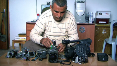 Emad Burnat and his five broken cameras in a scene from the Oscar® -nominated documentary 5 BROKEN CAMERAS, co-directed by Emad Burnat and Guy Davidi. A Palestinian-Israeli-French co-production. A Kino Lorber Release.
