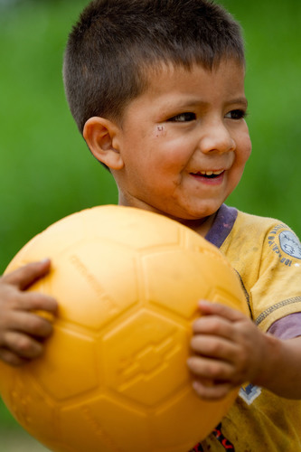 A little boy plays with a new, virtually indestructible football provided by Chevrolet in partnership with the One World Futbol Project  in Santa Gertrudis, El Salvador. The collaboration will result in the donation of 1.5 million footballs by Chevrolet to youth in war-stricken zones, refugee camps, disaster areas, and other disadvantaged communities around the word. The automaker's pledge will be fulfilled through a global network of organizations dedicated to helping empower the next generation of footballers. Its support is part of a ...