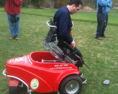 Disabled veteran uses a Paragolfer, a special mobility device that lifts people from a sitting position to a ...