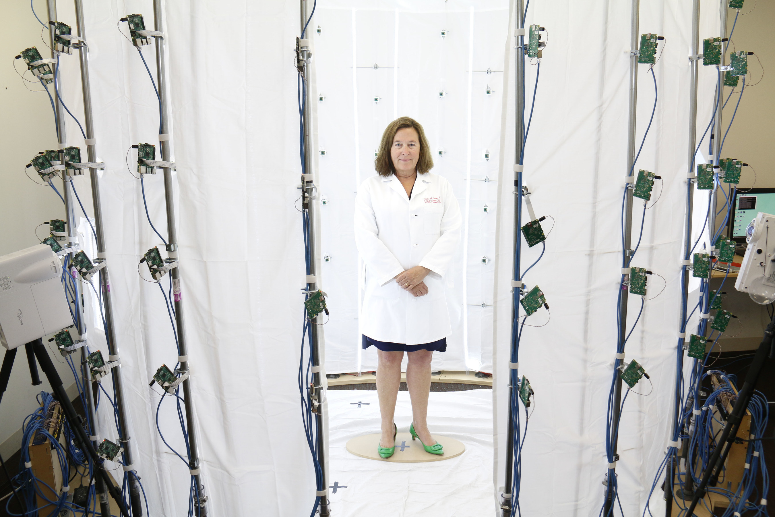 "Leslie Saxon, MD, founder and executive director of the USC Center for Body Computing stands inside the ""virtual doctor"" photo booth with 100 mini cameras taking a 360 degree image of her (technology created by USC Institute of Creative Technologies)"