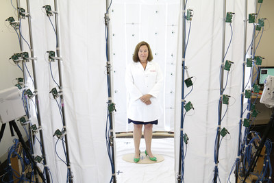 """Leslie Saxon, MD, founder and executive director of the USC Center for Body Computing stands inside the """"virtual doctor"""" photo booth with 100 mini cameras taking a 360 degree image of her (technology created by USC Institute of Creative Technologies)"""