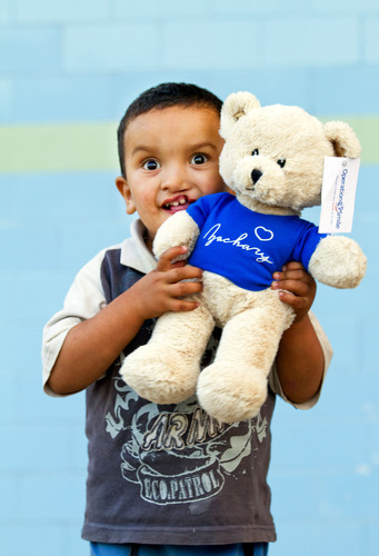 "A young boy with a cleft plays with his new ""Zachary"" teddy bear during an Operation Smile medical mission in Morocco. For every $240 donation this holiday season, Operation Smile is sending a teddy bear to a medical mission, and the donor will receive a commemorative bear for their very own.  (PRNewsFoto/Operation Smile, Marc Ascher)"