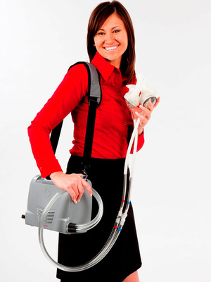 SynCardia Product Manager Karen Stamm holds the SynCardia temporary Total Artificial Heart while wearing the Freedom(R) portable driver, the world's first wearable power supply for the Total Artificial Heart. For added patient comfort and convenience, the Freedom driver is designed to be worn in the Backpack or Shoulder Bag (not pictured).  (PRNewsFoto/SynCardia Systems, Inc.)