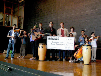 (Left to right above giant check:) Frank Derico, Executive Director of Neighborhood Studios, Andy Davis, Music Empowers Foundation, and Joan Rosenbaum, Studios Board member, celebrate $20,000 Music Empowers grant with Neighborhood Studios students.  (PRNewsFoto/Music Empowers Foundation)