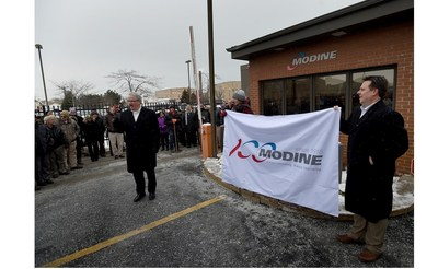 Brian Agen (r) and Peggy Kelsey (c) hold a new Modine flag as Tom Burke (l) addresses employees at the corporate headquarters in Racine, WI. The event kicked off the recognition celebration of Modine's 100th Anniversary. Copyright 2016, Gregory Shaver, The Journal Times.