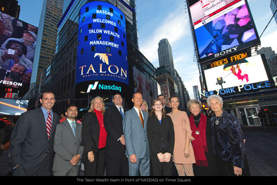 The Talon Wealth Team in front of the Talon Wealth logo in Times Square.