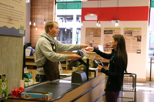 CLE student Thomas Schrank assists a customer at Dawson's Market in Rockville, Maryland.  ...