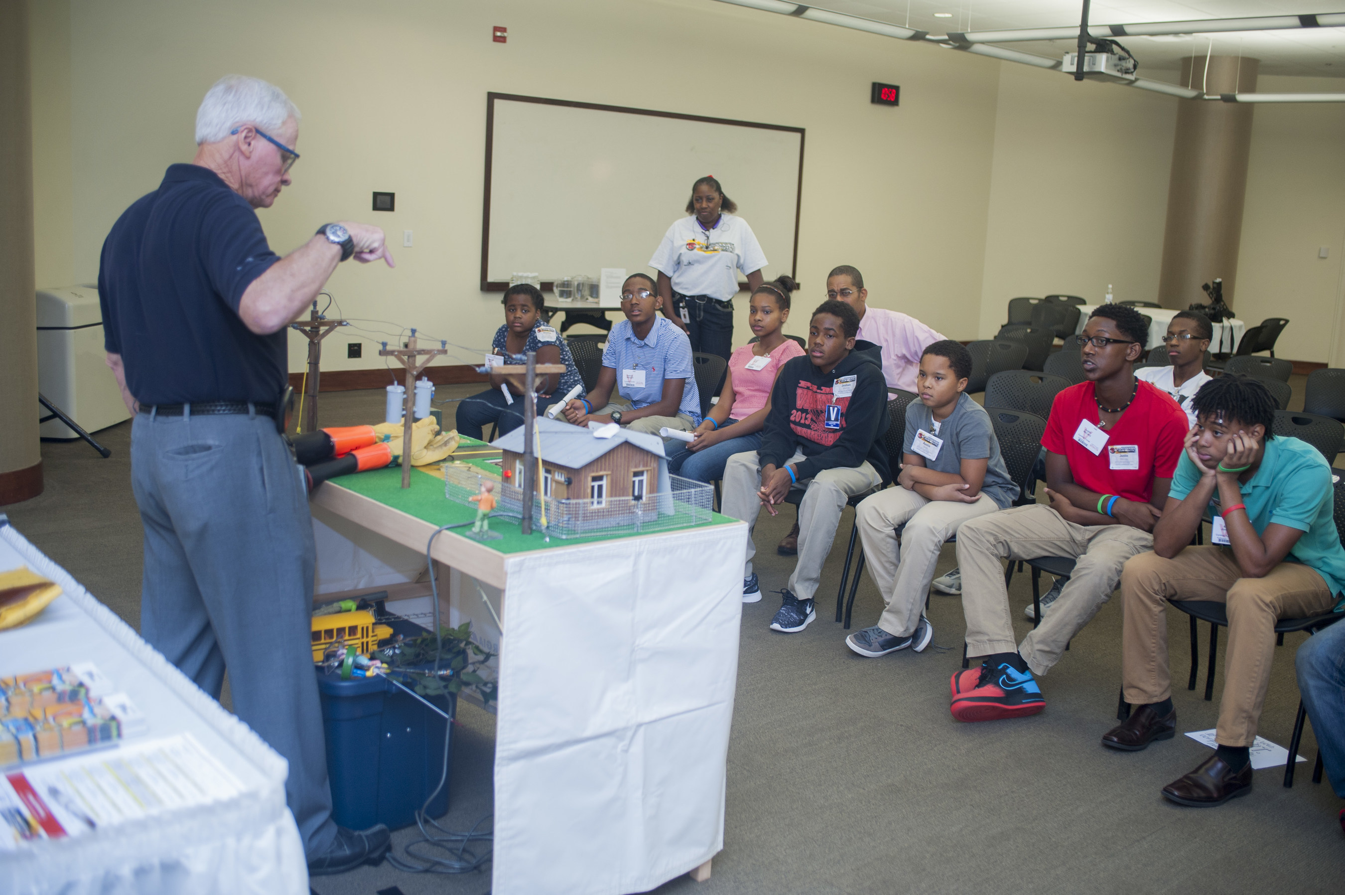 A Georgia Power PowerTOWN presenter talks to students about electrical safety using a model table town. The company has hosted more than 1,000 presentations over the past year.