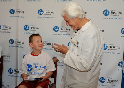 Bill Austin, Founder of the Starkey Hearing Foundation (right) provides the gift of hearing to a young patient at the Starkey Hearing Foundation Boston Red Sox Mission. More than 60 children and adults were fitted with a custom-made hearing aid - many experienced hearing for the very first time.  (PRNewsFoto/Starkey Hearing Foundation)