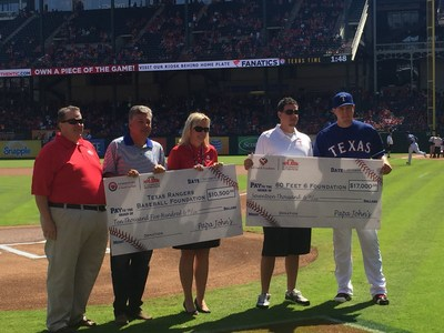 Steve McNeil, operations vice president at Papa John's presents checks to the Texas Rangers Baseball Foundation and 60 Feet 6 at the game on October 4.