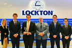 "Lockton's London Asset Management team proudly stands with their 2016 HFM Week Award for ""Best Insurance Broker."" Pictured from left are: Ashleigh Bratby, Drew Harvey, Henry Keville, Calvin Barnes, Dominic Pilgrim, and Oliver Leonard."
