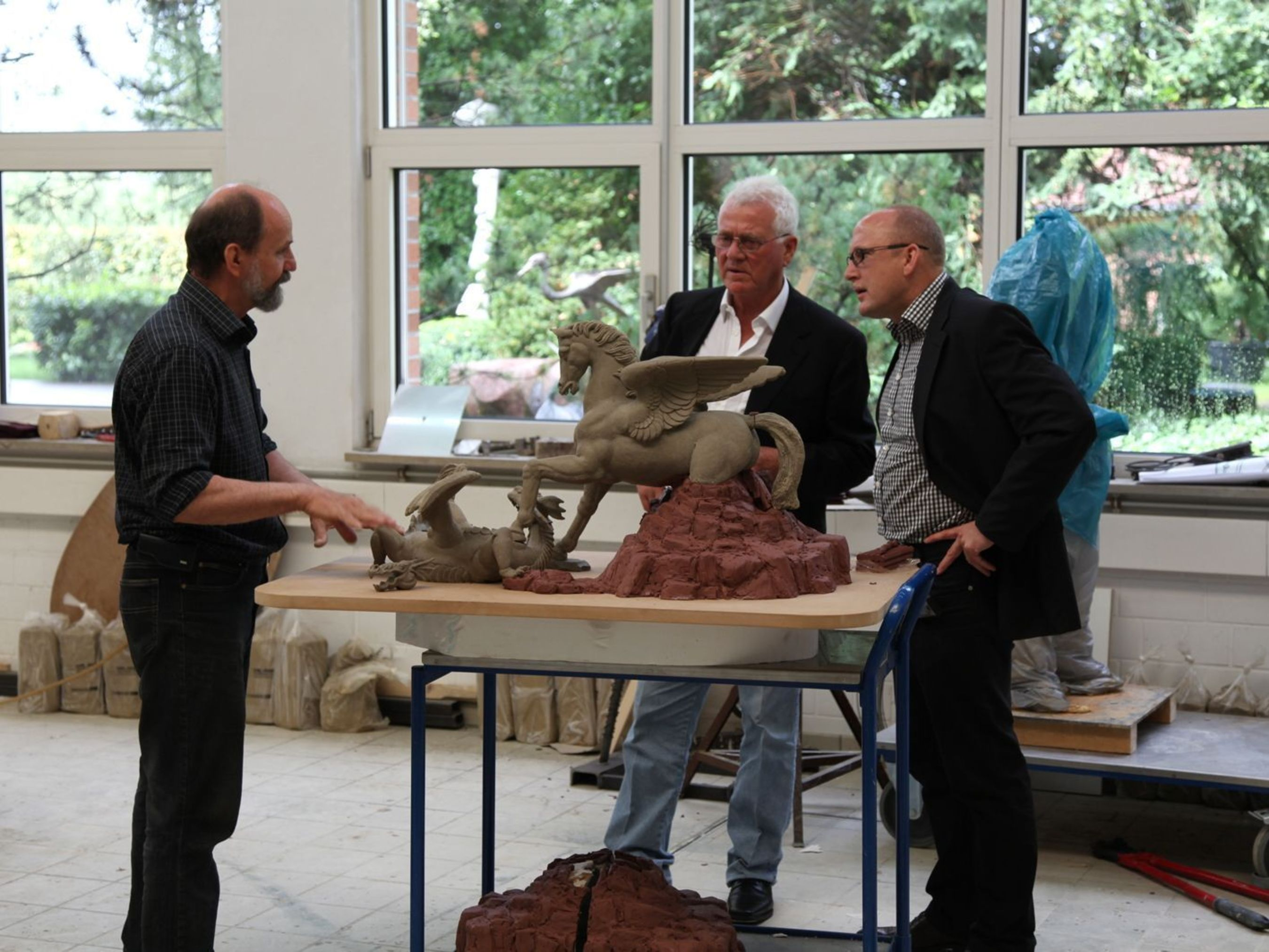 Complete Sculpture of Pegasus and Dragon / Frank Stronach (middle) with Guenter Czasny, deputy managing director from Strassacker, in a conversation with the academic sculptor Waldemar Schroeder (left) at Strassacker workshops. (PRNewsFoto/The Strassacker art foundry)