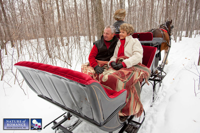 A couple enjoys a romantic horse-drawn sleigh ride through the woods in Door County, Wisconsin during the annual Nature of Romance promotion which runs through the end of March. Photo courtesy Mike Roemer/DoorCounty.com.