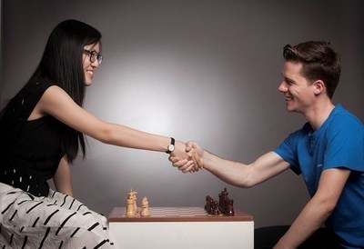 Women's Chess World Champion Hou Yifan and Tradimo Interactive Founder & CEO Sebastian J. Kuhnert shaking hands before a game of chess. (PRNewsFoto/Tradimo)