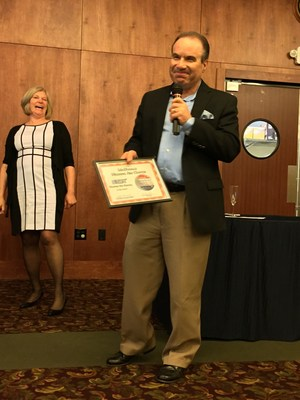 Mark Moore, CEO and Owner of McDonald Hearing Aid Center, accepting the award for McDonald Hearing Aid Center for being the Best Hearing Aid Center in Yolo County, California.