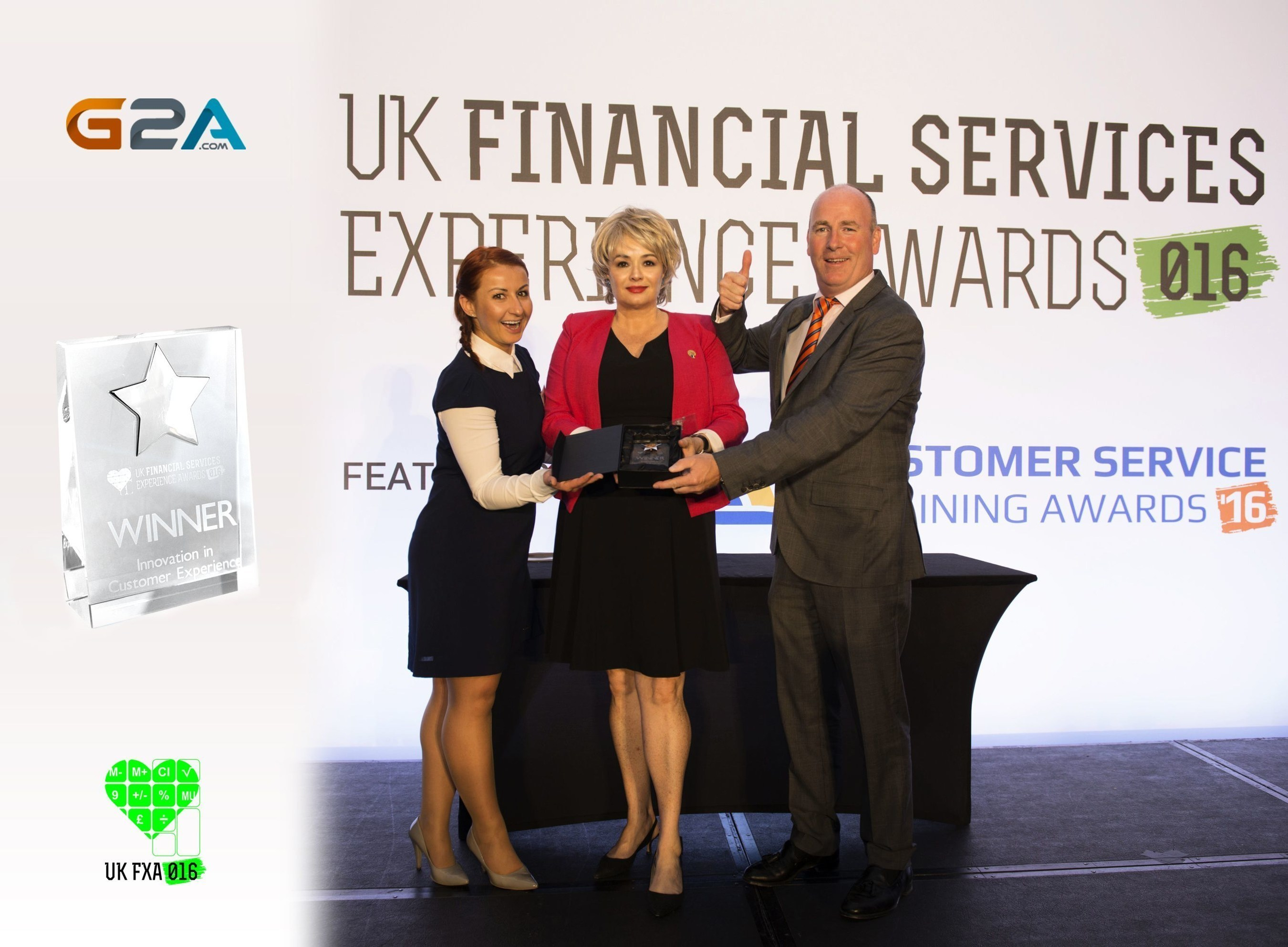 G2A is announced as a winner for the UK Financial Business Award ceremony in London (Neil Skehel,  Chief Executive Officer of #Awards International, Jacqueline Purcell - Head of Global Public Relations at G2A, receiving the 'Innovation in Customer Experience' award with Ewa Morawiec from Global PR at #G2A.COM) (PRNewsFoto/G2A.com)