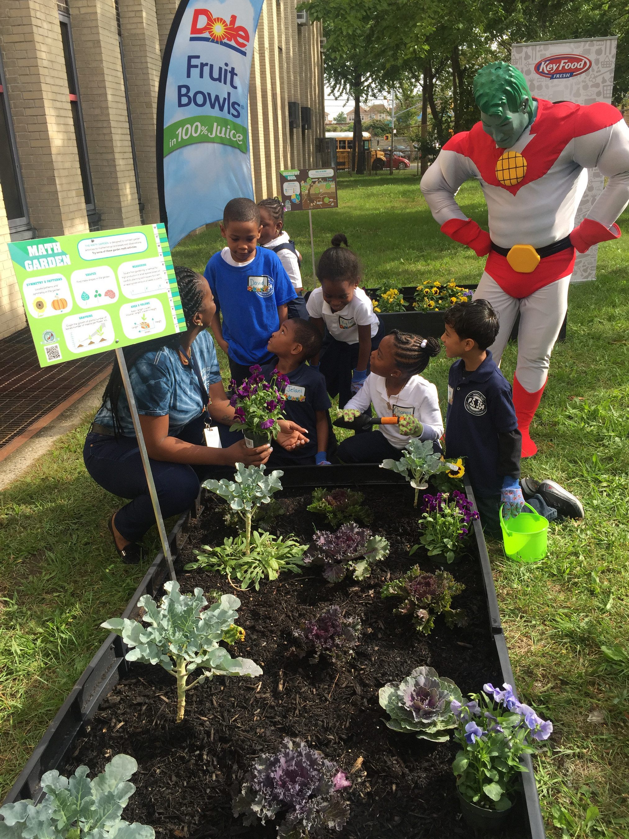 Kids from PS 354 STEM School of Queens learn first hand from their newly installed Learning Garden compliments of Dole Packaged Foods and Key Food as Captain Planet looks on.
