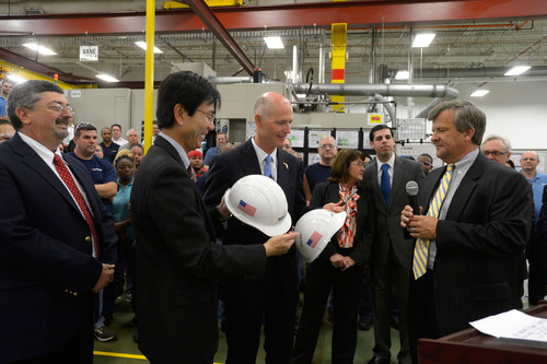 Florida Governor Rick Scott (center) is presented with ceremonial hard hats by Mitsubishi Power Systems Americas, Inc. executives following his tour of the company's Orlando manufacturing center where he announced that the state's unemployment rate has fallen below the national average while more than 280,000 private sector jobs have been created in Florida. Joining him on the plant tour are (left-to-right) Bob Provitola, MPSA's Orlando facility's General Manager, Koji Hasegawa, Mitsubishi Power Systems Americas president and ...