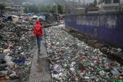 Save the Children is on the ground volunteer walks through piles of garbage after Hurricane Matthew reached Port-au-Prince. Canals, which are normally filled with garbage, flood and cover the streets. The photo was taken in Martissant neighborhood of Port-au-Prince. Photo Credit: Bahare Khodabande for Save the Children
