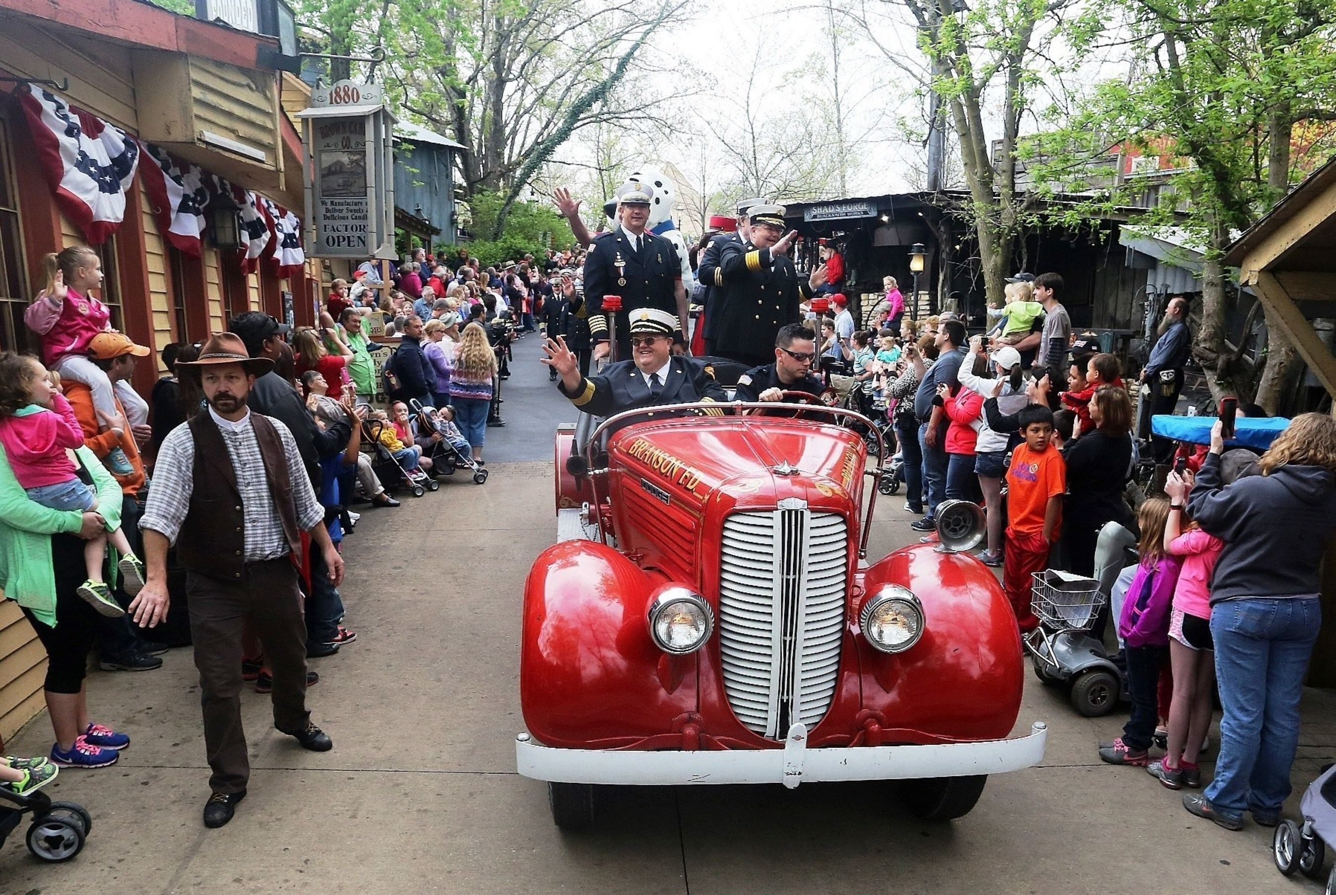 Uniformed firefighters led a parade through the streets of Silver Dollar City to Fireman's Landing, the theme park's new area with 10 family adventures, themed as a volunteer firefighter recruitment fair.
