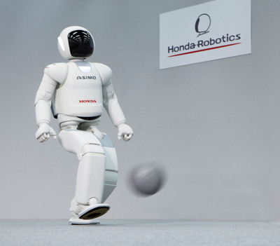 The new version of ASIMO demonstrates improved ability to kick a ball.