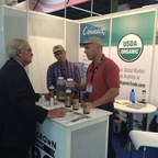 U.S./ Department of Agriculture Under Secretary for Farm and Foreign Agricultural Services Michael Scuse talks with Andy Wright (red shirt), owner of Minnesota-based Acme Organics, and David Wright about the organic Triple Crown BBQ Sauce at the Anuga Food Show this fall in Germany.