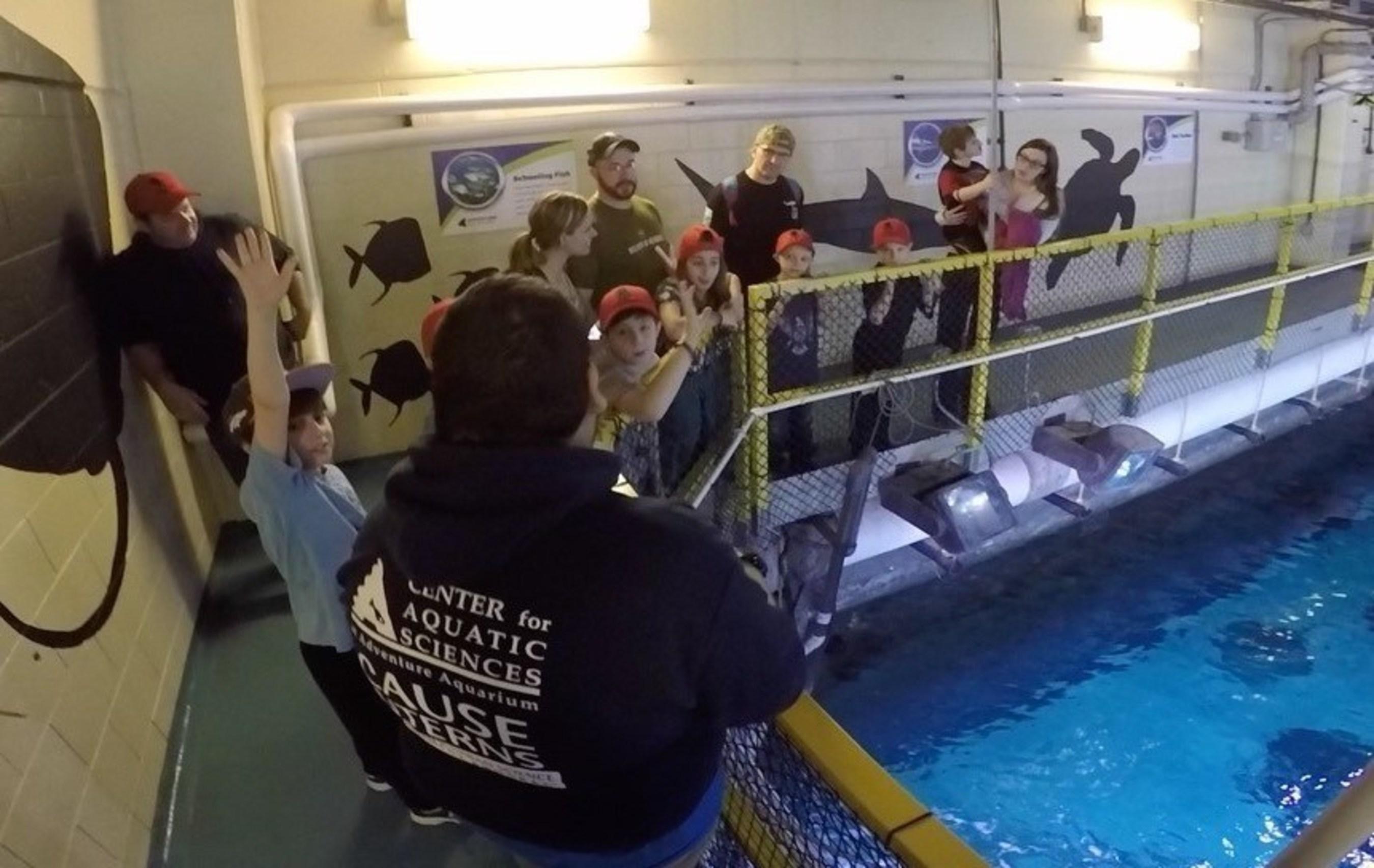 Families of injured service members tour behind the tanks at Adventure Aquarium.