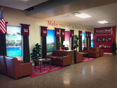The Fulton Homes living room at Phoenix-Mesa Gateway Airport welcomes out-of-town visitors near the baggage claim with cozy couches and coffee tables, interactive QR-coded photos, and faux views of the Arizona landscape.  (PRNewsFoto/Fulton Homes Corporation)