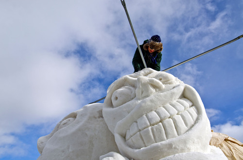 A member of Team Great Britain-Wales works on their piece at the 2013 International Snow Sculpture ...