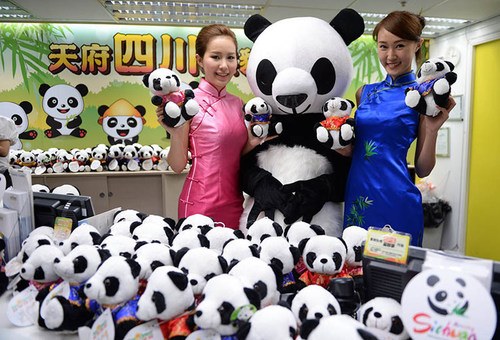 Two models presents panda dolls in the Sichuan tourism product hall in Causeway Bay in Hong Kong on July 10. ...