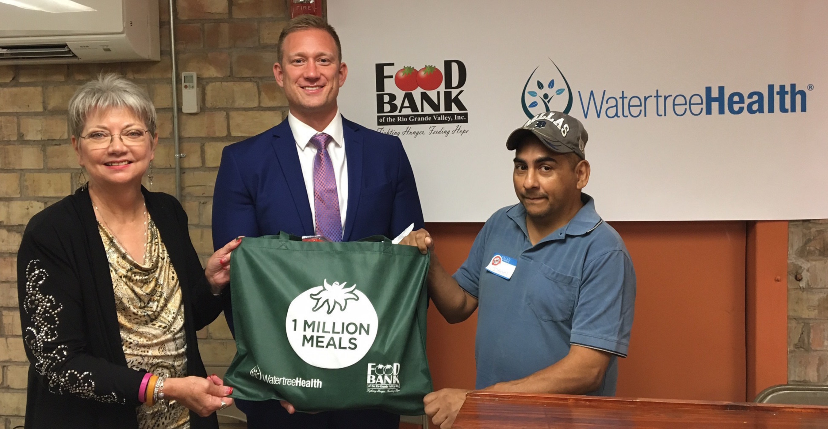 CEO of the Food Bank of the Rio Grande Valley Terri Drefke and Watertree Health President Shane Power present the One Millionth Meal to Food Bank RGV Client Mr. Torres Jr. at a press conference held today at Food Bank RGV, as part of the celebration of Two Million Meals.