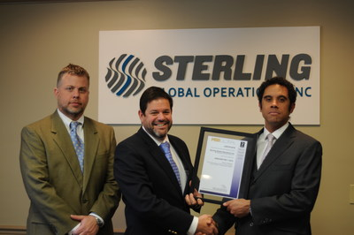 Jeremy Duncan, Sterling Global Operations (SGO) vice president of operations, and Alan Weakley, SGO president and chief operating officer, receive from Tony Phipps, director of United Kingdom-based MSS Global, SGO's designation as the first American company to receive worldwide certification under ANSI/ASIS PSC.1-2012, an international standard designed specifically for private security company quality management systems.