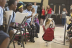 "Save the Children Animal Ambassador Lassie carries a disaster supply kit into a Save the Children ""Prep Rally"" at the Treme Community Center in New Orleans on Thursday. Photo by Lee Celano/Getty."