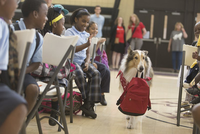 """Save the Children Animal Ambassador Lassie carries a disaster supply kit into a Save the Children """"Prep Rally"""" at the Treme Community Center in New Orleans on Thursday. Photo by Lee Celano/Getty."""
