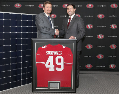 SunPower CEO Tom Werner delivers the first high-efficiency SunPower solar panel to San Francisco 49er CEO, Jed York.  SunPower is the official and exclusive solar technology partner of the San Francisco 49ers and the new Santa Clara Stadium.  SunPower high-efficiency solar panels will be featured in three solar array-covered bridges, a solar canopy above the green roof on the suite tower portion of the stadium and over the 49ers training facility. The solar panels will be produced at SunPower's Silicon Valley manufacturing facility.  (PRNewsFoto/SunPower Corp.)